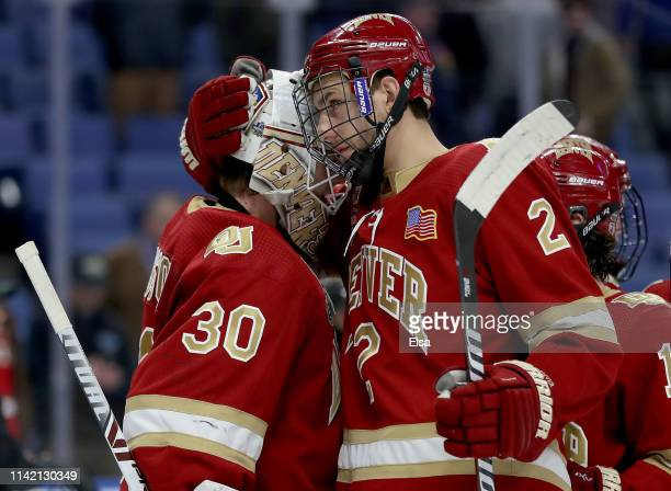 Filip Larsson of the Denver Pioneers is consoled by Erich Fear after the overtime loss to the Massachusetts Minutemen during the semifinals of the...