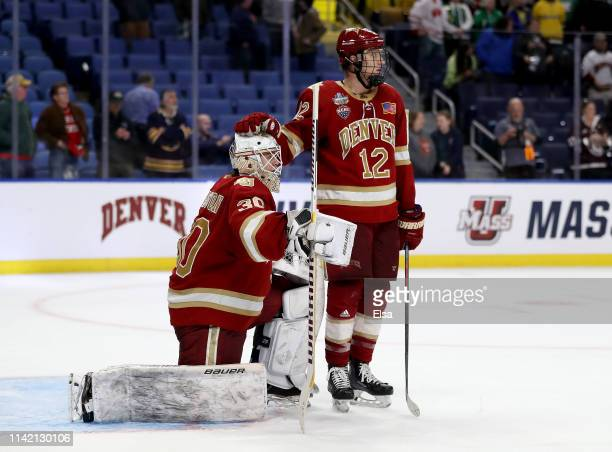 Filip Larsson of the Denver Pioneers is consoled by Kohen Olischefski of the Denver Pioneers after the overtime loss to Massachusetts Minutemen...