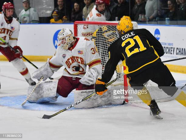 Filip Larsson of the Denver Pioneers stops a American International Yellow Jackets' shot as Justin Cole of the Yellow Jackets waits for a rebound...