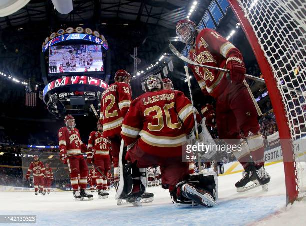 Filip Larsson,Jarid Lukosevicius and Kohen Olischefski of the Denver Pioneers react to the overtime loss to the Massachusetts Minutemen during the...