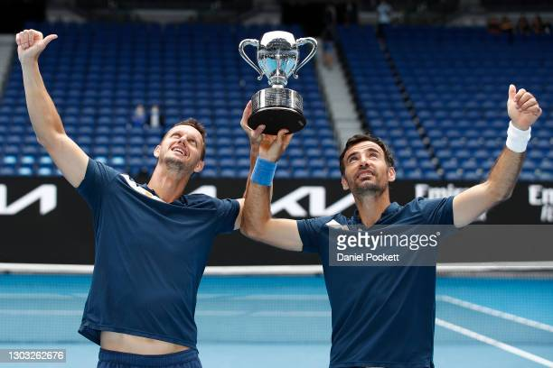 Filip Polasek of Slovakia and Ivan Dodig of Croatia pose with the championship trophy after winning their Men's DoublesFinal match against Joe...