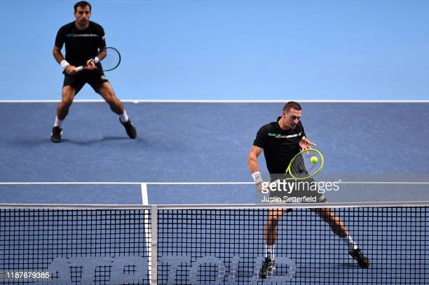 Filip Polasek of Slovakia, playing partner of Ivan Dodig of Croatia plays a backhand volley in their doubles match against Raven Klaasen of South...