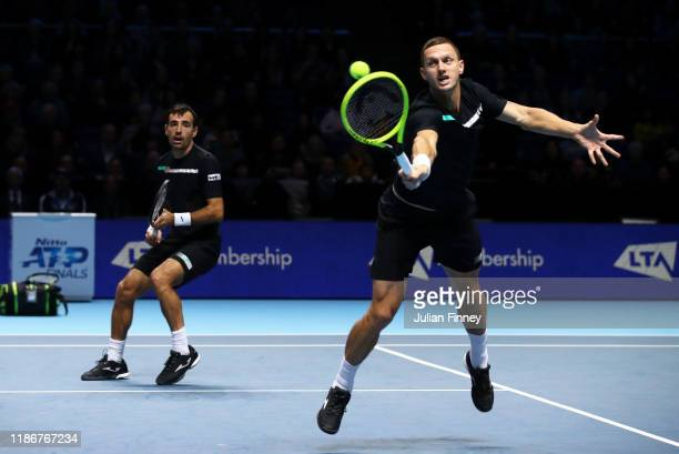 Filip Polasek of Slovakia, playing partner of Ivan Dodig of Croatia stretches to play a backhand in their doubles match against Lukasz Kubot of...