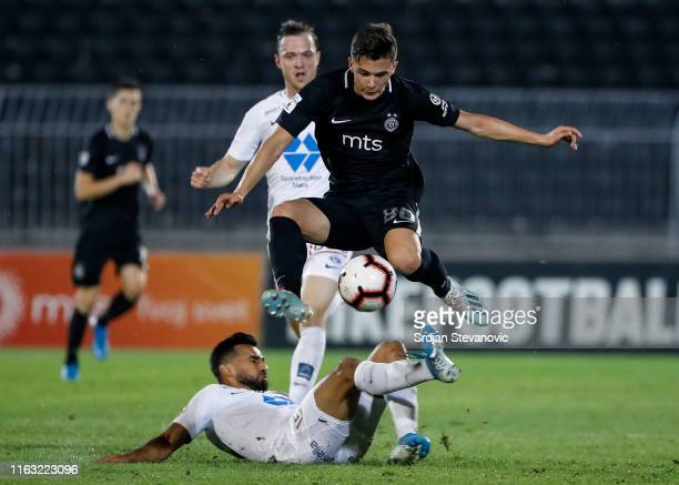 Filip Stevanovic of Partizan jumps over Etzaz Hussain of Molde during the UEFA Europa League Play Off First Leg match between Partizan Belgrade and...