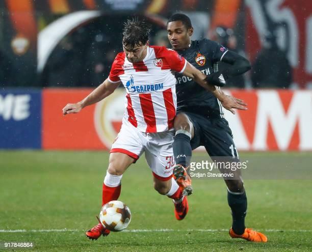 Filip Stojkovic of Crvena Zvezda in action against Vitinho of CSKA Moscow during UEFA Europa League Round of 32 match between Crvena Zvezda Belgrade...