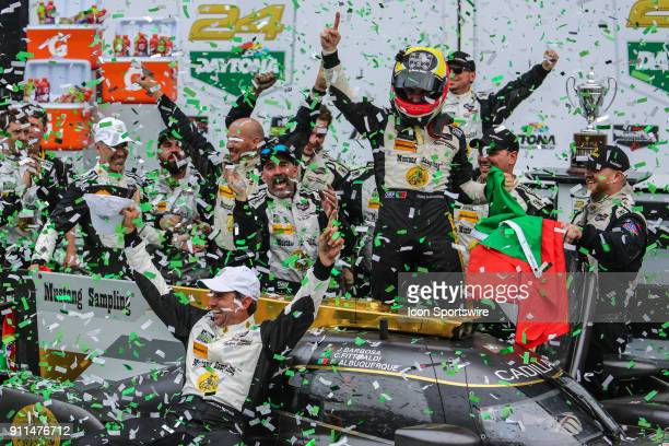 Filipe Albuquerque driver of the Mustang Sampling Racing Cadillac DPiVR celebrates with teammates in Victory Lane following the Rolex 24 at Daytona...