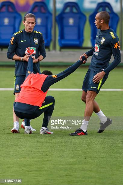 Filipe Luis and Miranda help Neymar Jr to stand up during a training session of the Brazilian national football team at the squad's Granja Comary...