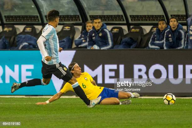 Filipe luis Kasmirski of the Brazilian National Football Team slides to get the ball after a contest with Carlos Joaquin Correa of the Argentinan...