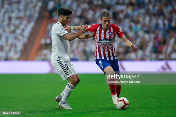 Filipe Luis of Atletico de Madrid competes for the ball with Juan Marco Asensio of Real Madrid CF during the La Liga match between Real Madrid CF and...