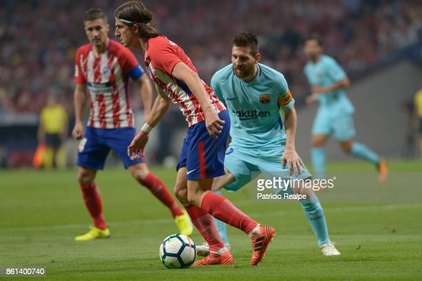 Filipe Luis of Atletico de Madrid fights for the ball with Lionel Messi of Barcelona during a match between Atletico Madrid and Barcelona as part of...