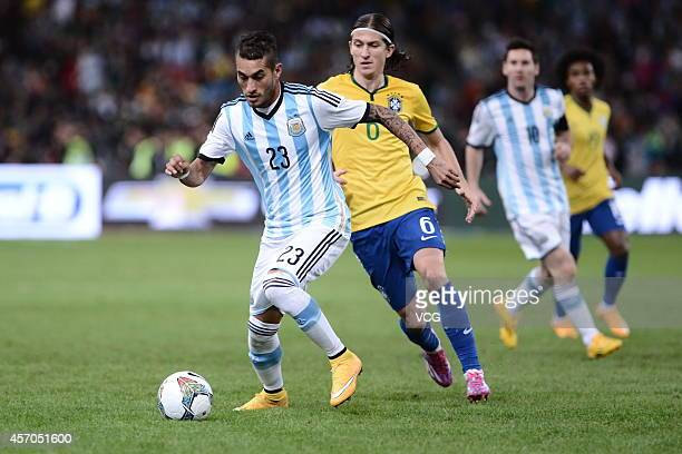 Filipe Luis of Brazil and Roberto Pereyra of Argentina battle for the ball during a match between Argentina and Brazil as part of 2014 Super Clasico...