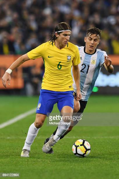 Filipe Luis of Brazil controls the ball from Paulo Dybala of Argentina during the Brasil Global Tour match between Brazil and Argentina at Melbourne...