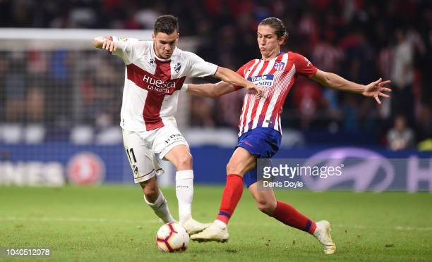Felipe Luis of Club Atletico de Madrid is tackled by Alex Gallar of SD Huesca a during the La Liga match between Club Atletico de Madrid and SD...
