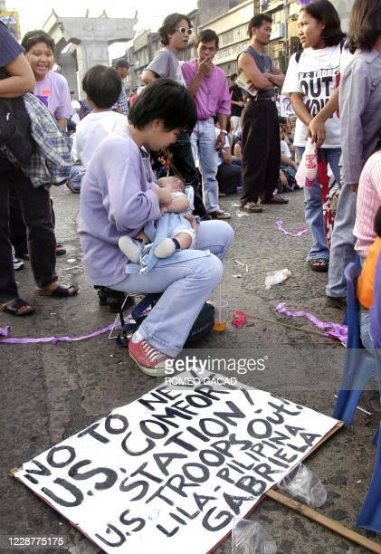 Filipina activists breast feeds her baby as she participate in the rally near the Malacanang presidential palace in Manila, 08 March 2002, to mark...