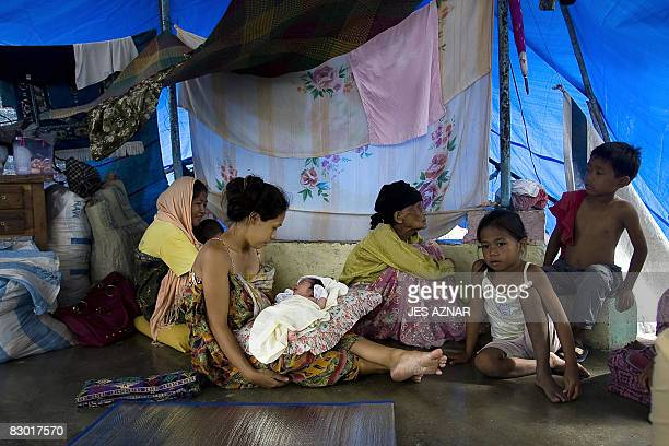 Filipina evacuee Arbaya Musalip gently cradles her three-day-old daughter, swaddled in a piece of old cloth amid the chaos of this filthy evacuation...