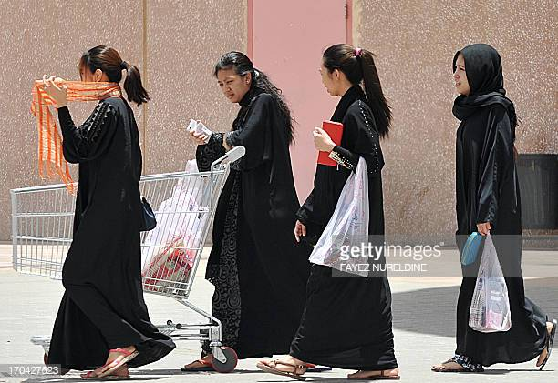 Filipina maids carry shopping bags as they walk out of a mall in Riyadh, on June 12, 2013. A three-month reprieve ended for Fhilipino death row...