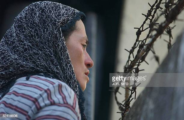 Filipina Muslim woman looks over the prison barb wire fence in an effort to find her relative after police commandos stormed the Camp Bagong Diwa...