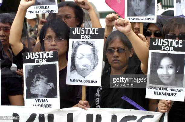 Filipina protestors from Gabriela Women's Party dressed in black carry portraits of slain women activists during a rally outside the armed forces...