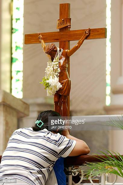 Filipina shows reverence to a crucifix as part of religious celebrations marking Black Saturday in Manila 10 April 2004 The country is over 80...