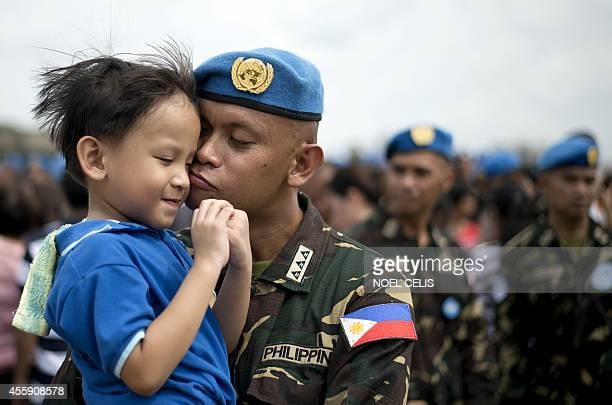 Filipina UN peacekeeper kisses his son during a send-off ceremony at the Villamor Airbase in Manila on September 22, 2014. The 157 soldiers will be...