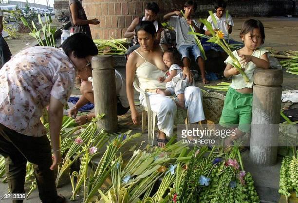 Filipina vendor sells palm fronds for Sunday mass on a Manila sidewalk while nursing her daughter 04 April 2004 Lenten Sunday in the Roman Catholic...