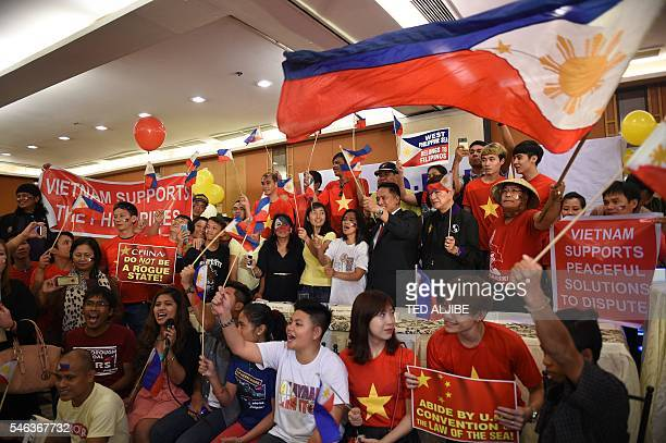 Filipino activists and Vietnamese nationals hold placards and wave Philippine flags as they anticipate a favourable decision from a UN tribunal...