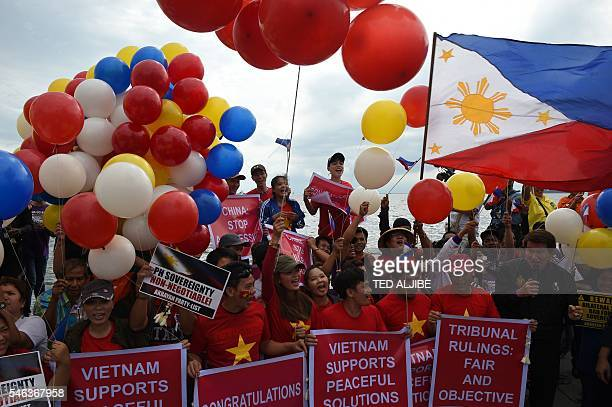 Filipino activists and Vietnamese nationals release balloons and wave Philippine flags as they anticipate a favourable decision from a UN tribunal...