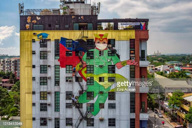 """Filipino artists from the group """"Art Attack"""" paint a mural depicting Darna, a fictional Filipino comics superhero, wearing a scrub suit and..."""
