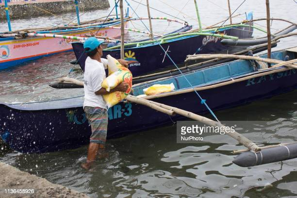 A Filipino boatman loads a sack of rice on a boat in Masinloc township Zambales province north of Manila Philippines on Friday 12 April 2019