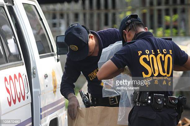 Filipino bomb experts investigate at the scene where a homemade bomb exploded on a passenger bus on October 21 2010 in the southern Philippine...