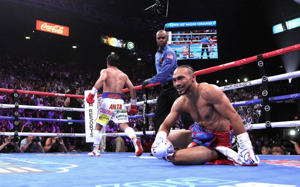Filipino boxer Manny Pacquiao heads to a neutral corner as US boxer Keith Thurman struggles to get up after being knocked down during the first round...