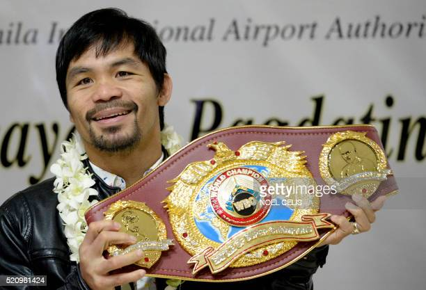 Filipino boxer Manny Pacquiao holds his championship belt as he arrives at the Manila International Airport in Manila on April 14 2016 Pacquiao...
