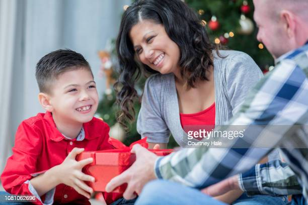 filipino boy exchanging christmas gifts with parents at home - filipino christmas family stock pictures, royalty-free photos & images