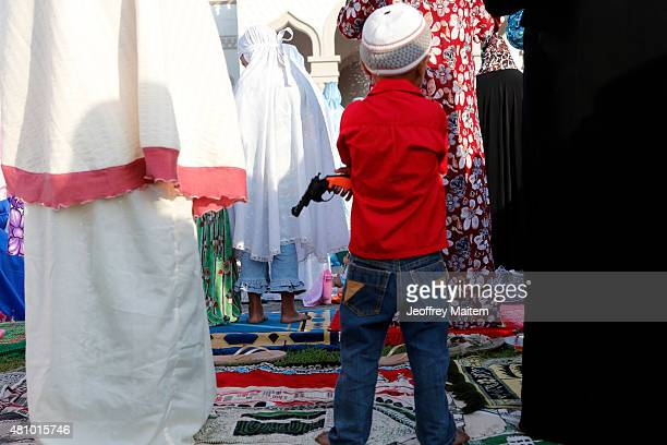 Filipino boy holds a toy gun while his mother prepare for their congressional prayer at the Grand Mosque also known Sultan Haji Hassanal Bolkiah...