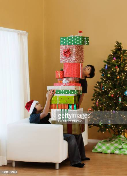 Filipino boys sitting with stack of Christmas gifts