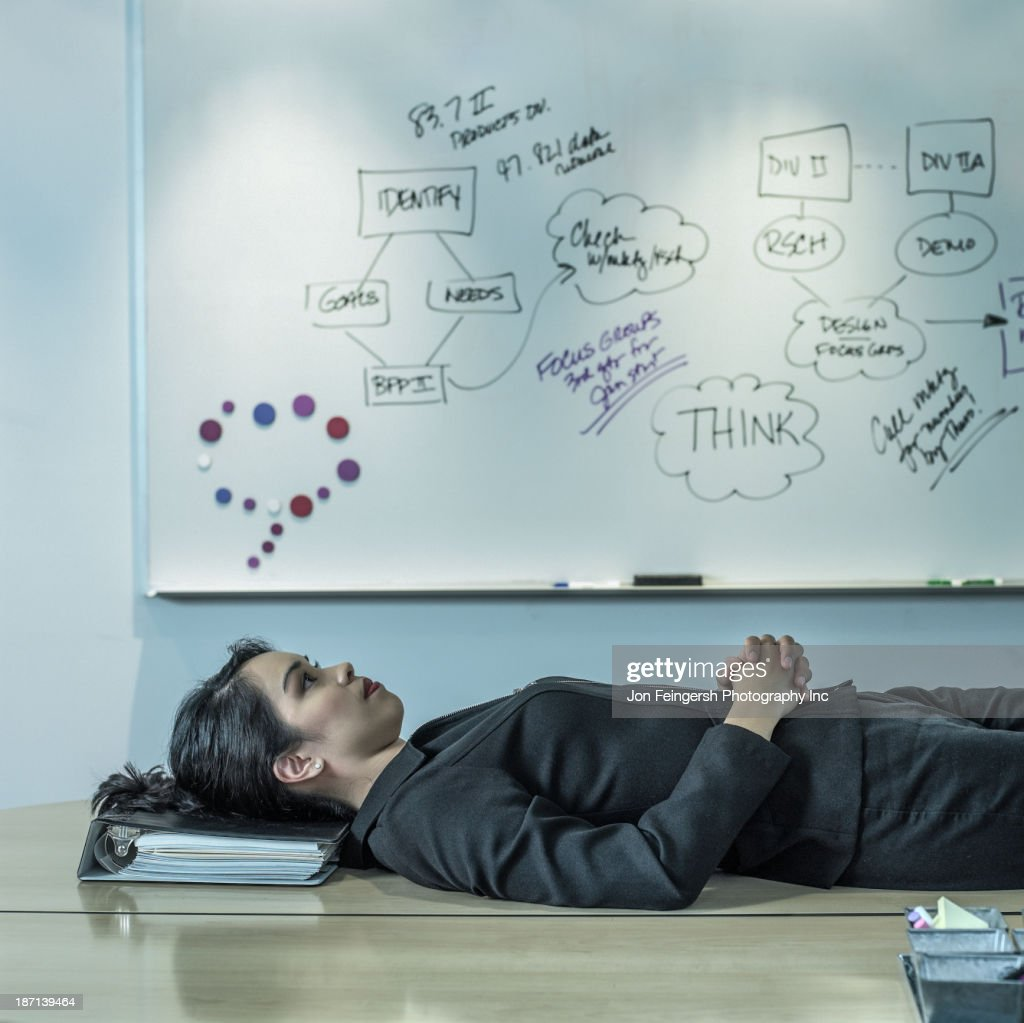 Filipino businesswoman laying on desk : Stock Photo