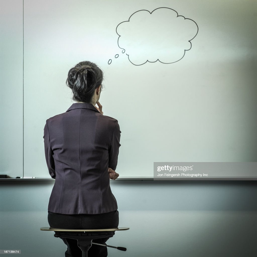 Filipino businesswoman with thought bubble in office : Stock Photo