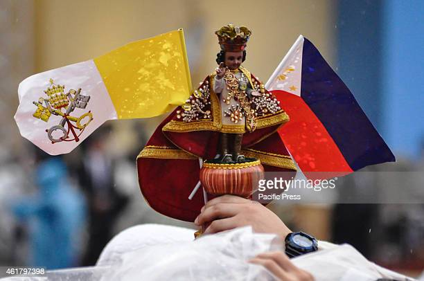 Filipino Catholic raises an image of the Santo Niño and Vatican and Philippine flaglets during the 'Encounter with Youth' in University of Santo...