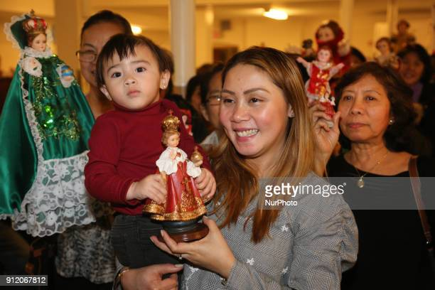 Filipino Catholics carry their statues of Santo Niño while they dance during the Sinulog procession celebrating the Feast of Santo Niño de Cebú in...