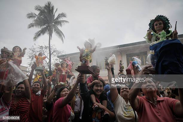 Filipino Catholics raise their Santo Nino statues as they are sprayed with holy water during the Feast of Santo Nino at a church in the poor district...