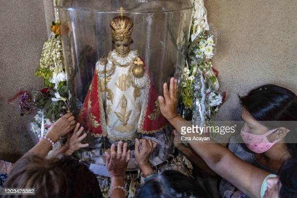 Filipino Catholics wearing protective masks touch an image of Baby Jesus during Ash Wednesday services at a church on February 26 2020 in Paranaque...