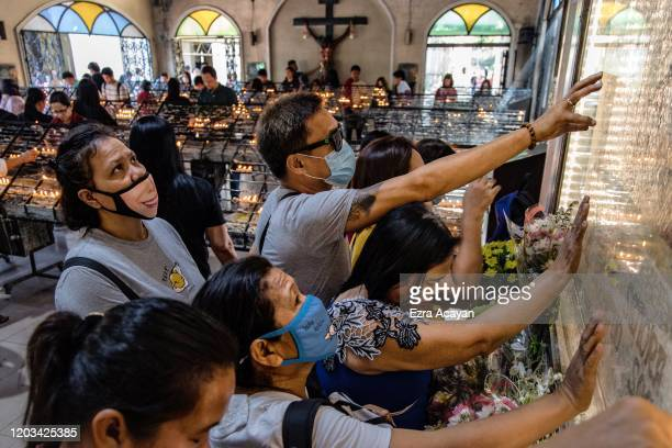 Filipino Catholics wearing protective masks touch an image of Mother Mary during Ash Wednesday services at a church on February 26 2020 in Paranaque...