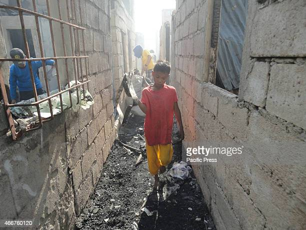 Filipino child carries a piece of metal at Barangay Tonsuya where it will be sold for cash Two people were killed and four firemen were injured as...