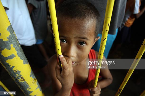Filipino child displaced by floods waits to receive food from the government at the evacuation center following a recent typhoon on December 21 2011...