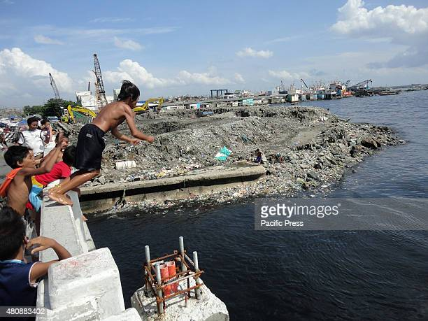 Filipino child dives towards the Manila Bay, as he is cajoled by his friends, in Navotas City, north of Manila, Philippines.