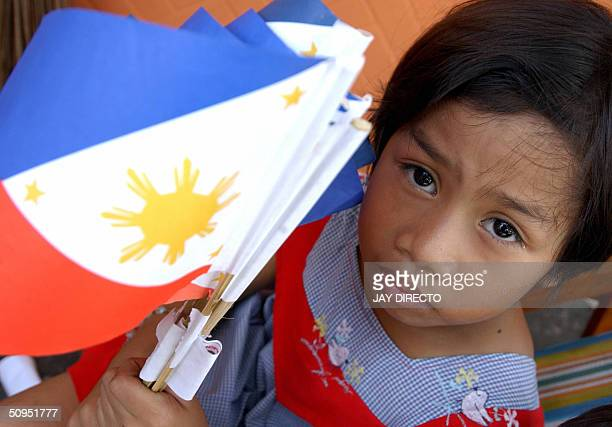 Filipino child holds a philippine flag in Manila 12 June 20004 as The Pilippines marks 106th anniversary of Independence Day amid heightened security...