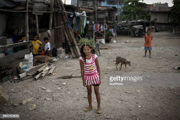 A Filipino child plays with a wreath at a landfill community in Muntinlupa southeast of Manila Philippines March 25 2014 According to the...