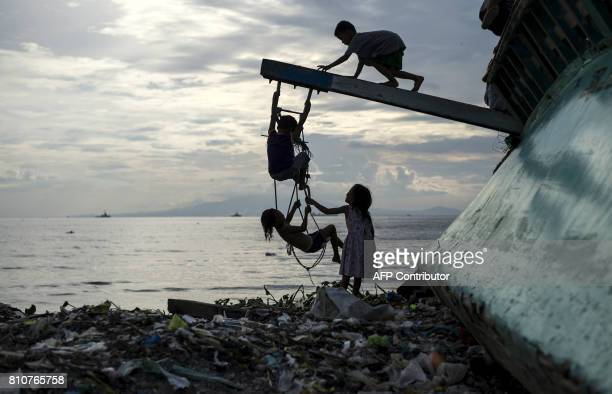TOPSHOT Filipino children play at a broken fishing boat in garbage filled Manila Bay in Baseco Tondo on July 8 2017 / AFP PHOTO / NOEL CELIS