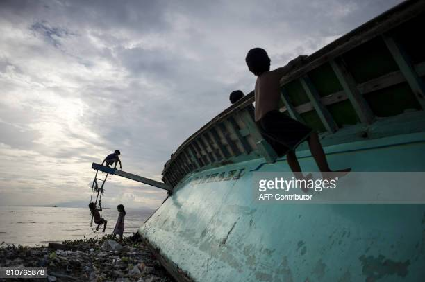 Filipino children play at a broken fishing boat in garbage filled Manila Bay in Baseco Tondo on July 8 2017 / AFP PHOTO / NOEL CELIS