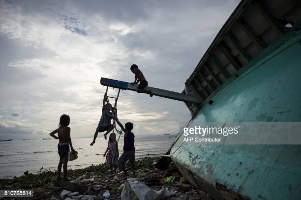 Filipino children play at a broken fishing boat in the garbage filled Manila Bay in Baseco Tondo on July 8 2017 / AFP PHOTO / NOEL CELIS